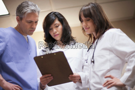 female doctors and surgeon reading file