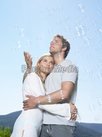 couple in sun catching bubbles