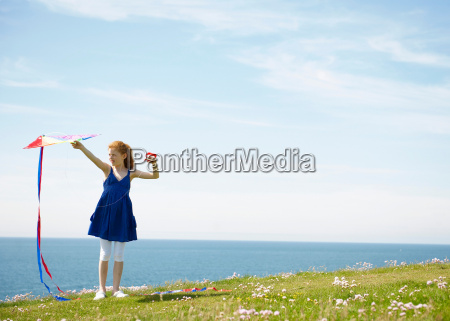 young girl with kite by ocean