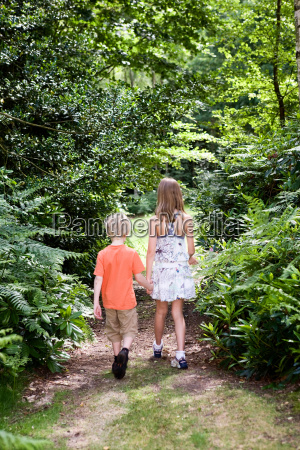 boy and girl walking through forest