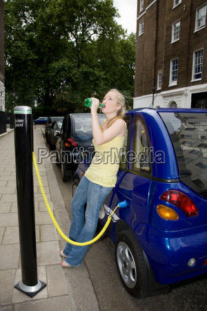 young woman drinking by electric car