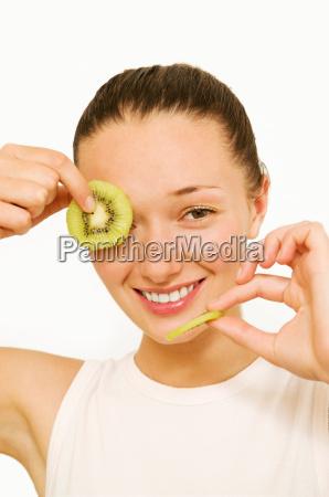 girl holding kiwi slices smiling