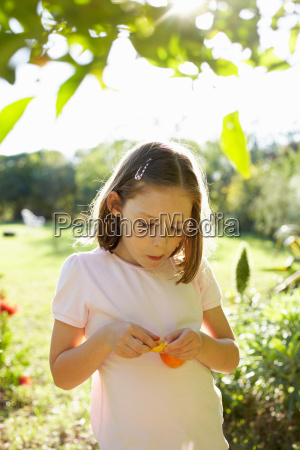 young girl outside eating fruit