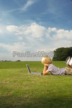 boy looking at laptop in field