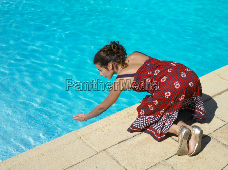 girl testing pool water