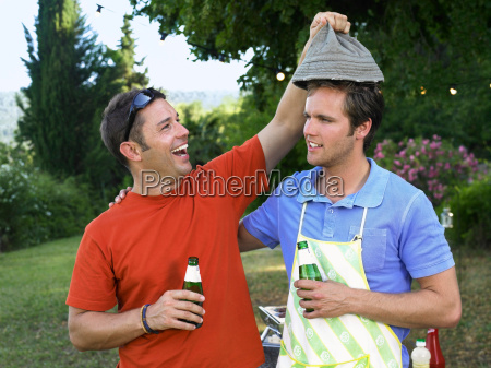 two men laughing at barbecue