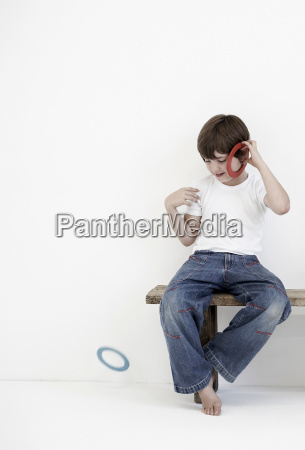 young boy playing with plastic rings
