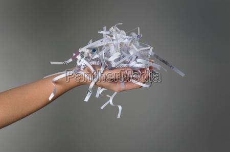 female hand holding shredded paper