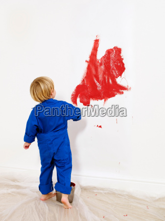 toddler boy painting wall red