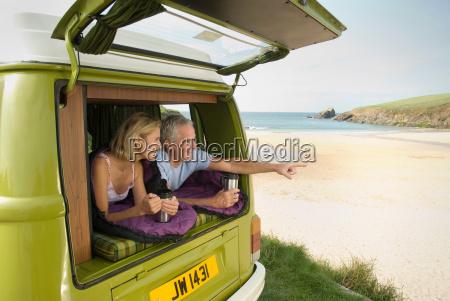 mature couple lying in camper van