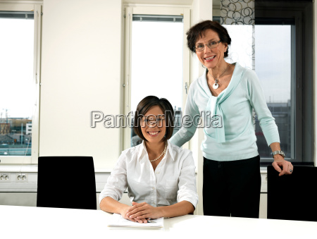 business women by conference table
