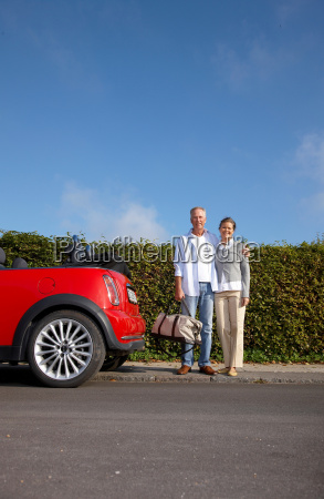 mature couple standing next to car