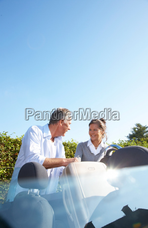 mature couple putting bags into car