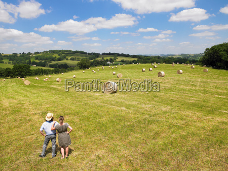 man and woman standing in field