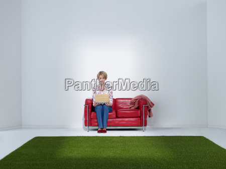 woman with laptop in green office