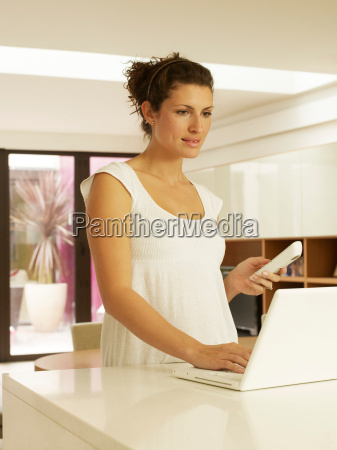 woman using laptop on kitchen work