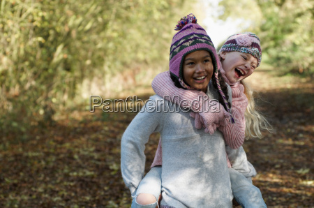 girl carrying friend in countryside