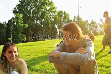 friends sitting in grass in park