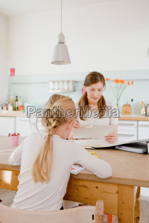 girl and woman sitting at table
