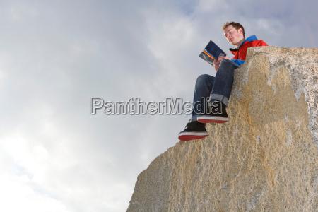 man reading on mountain top