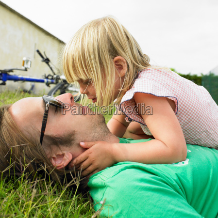 father and daughter laying on grass