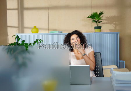 woman yawning at desk in office