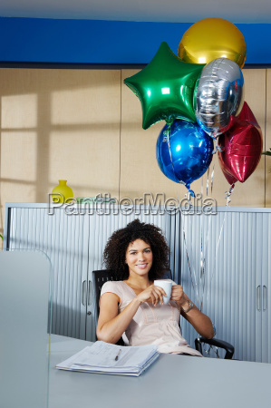 young woman with balloons in office