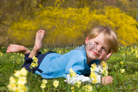 boy lying in grass with spring