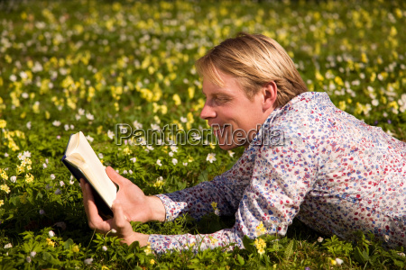 man reading in grass with spring