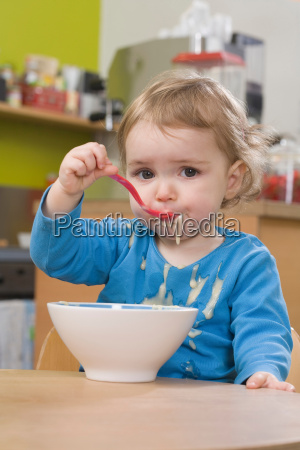 young girl eating and spilling pudding