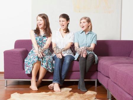 three women on a sofa screaming