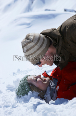 young couple lying in snow