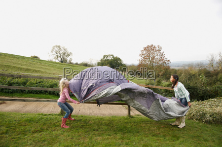 two girls putting up tent
