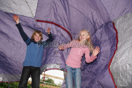 boy and girl playing under tent