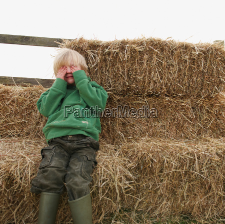 boy hiding eyes on hay bales