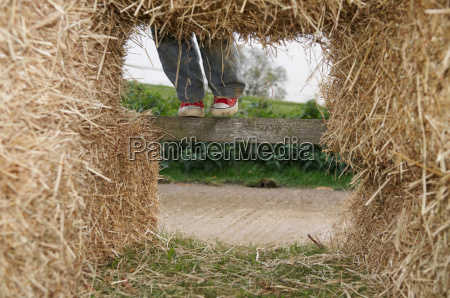 boy climbing in hay bales
