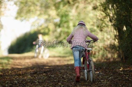girl walking bike up country lane