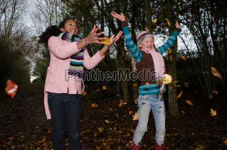 girls throwing autumn leaves