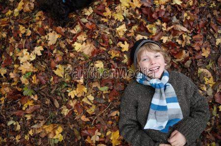 boy lying on autumn leaves