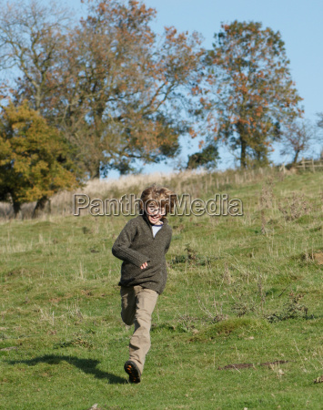 young boy running in countryside