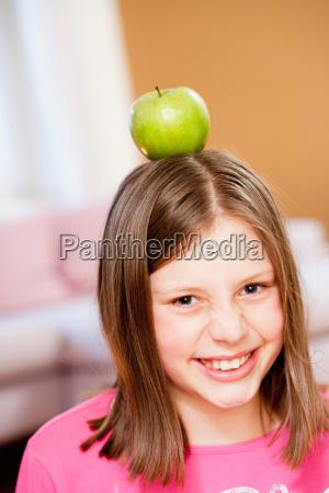 girl balancing apple