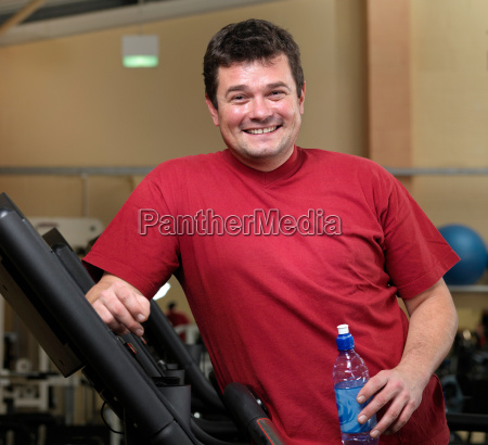 man relaxing on running machines at
