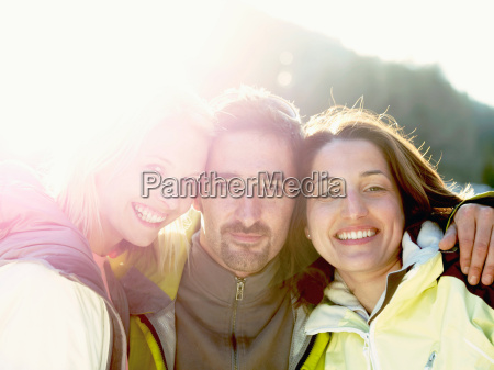 three friends in snow on hillside