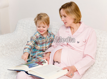 pregnant woman and boy reading book
