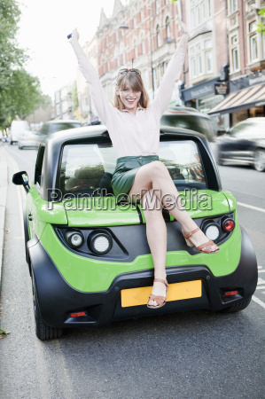 woman sitting on car on city