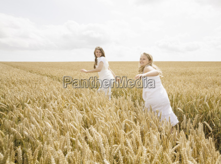 girls running in wheat field