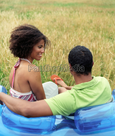 couple sitting on blow up sofa