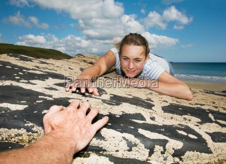 woman reaching across rocks to man