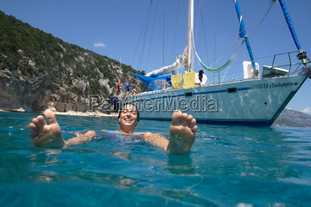 woman swimming next to moored boat