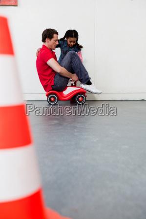 young girl teaching man to ride